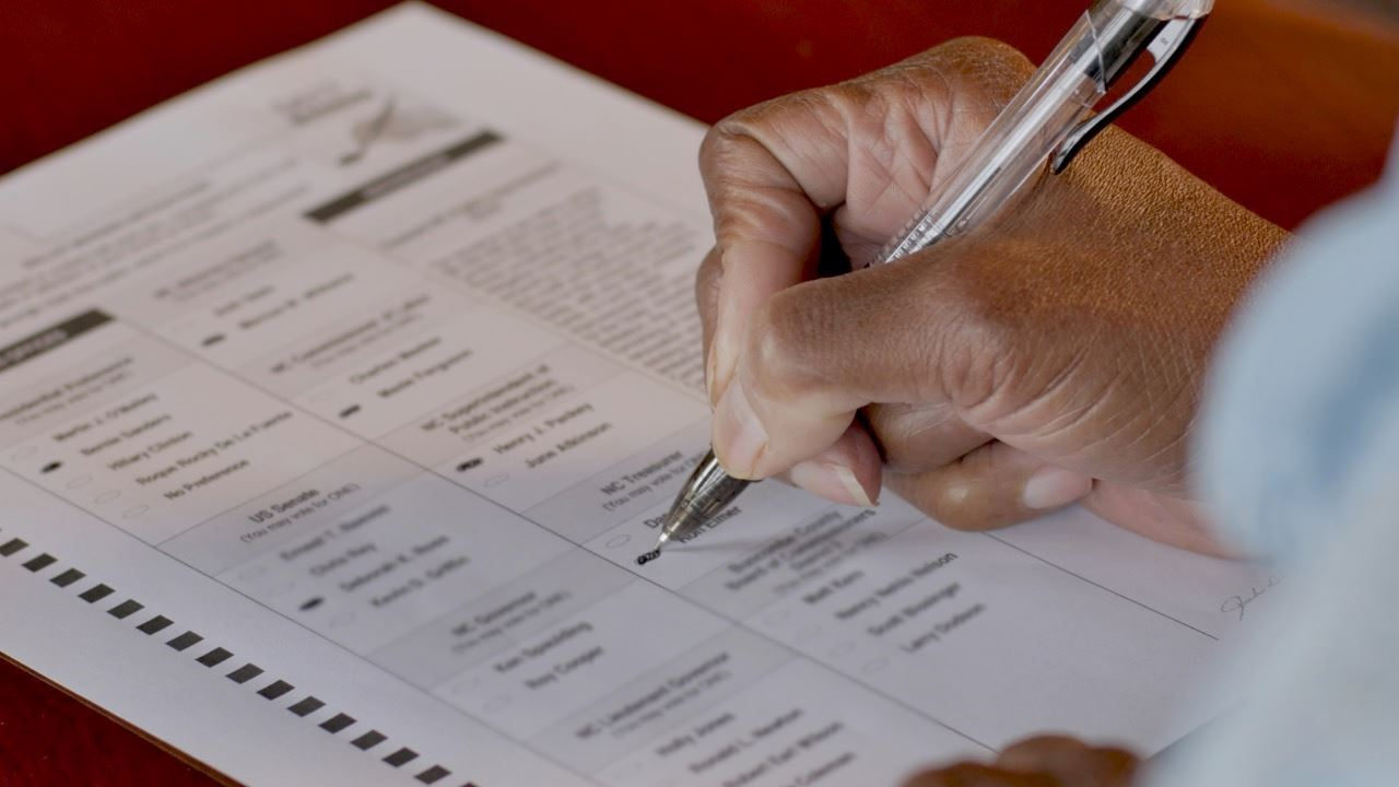 Hand filling out an absentee ballot
